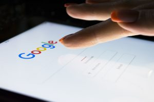 Woman with her finger over the Google search bar on her mobile device, about to make a search. Coronavirus search trends help us understand shifting consumer behavior.