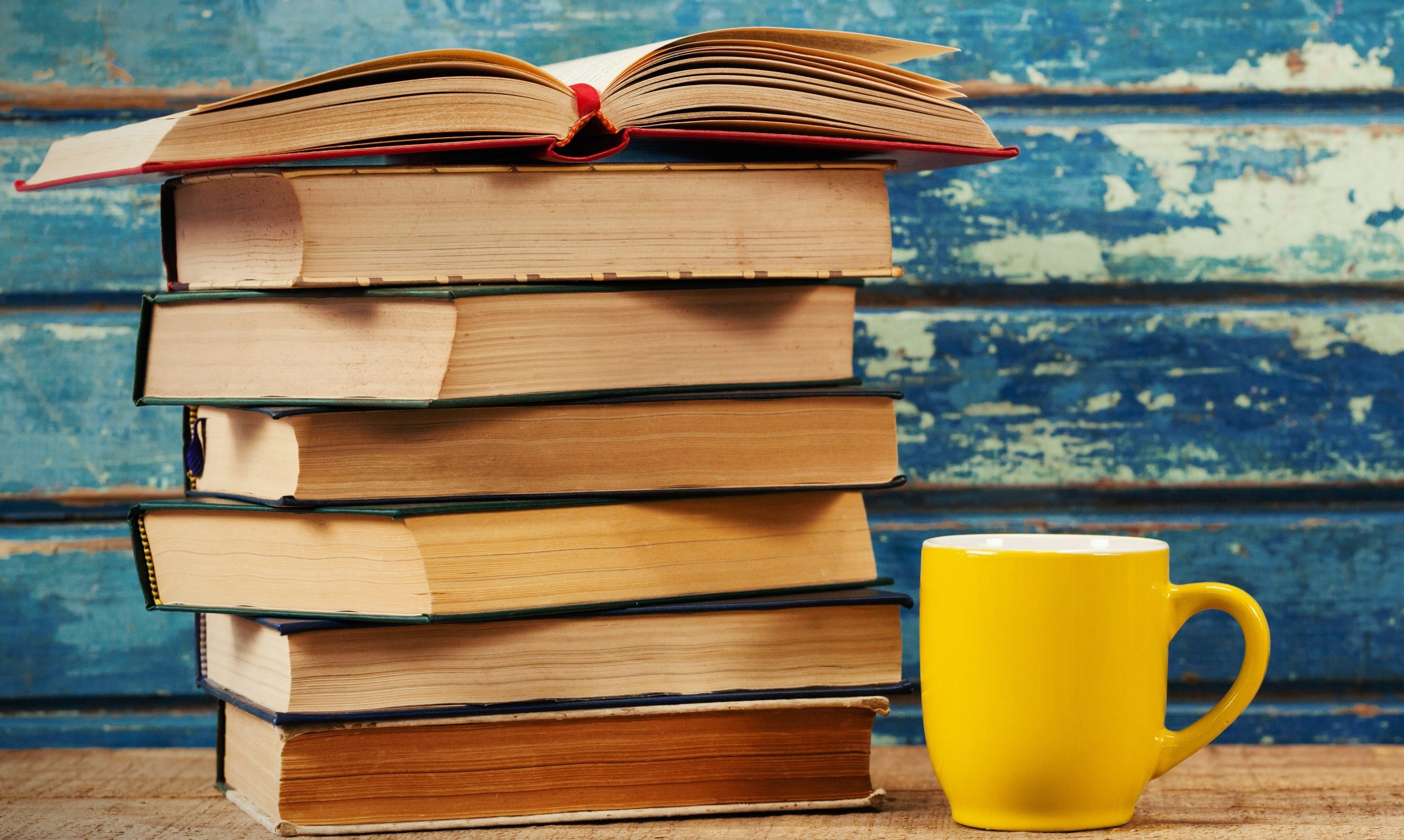 A stack of marketing strategy books is sitting next to a yellow coffee mug. There is a blue wood background.